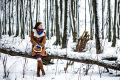 Beautiful woman in sheepskin coat sitting on tree branch in winter forest Royalty Free Stock Photography