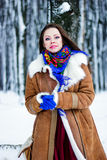 Beautiful woman in sheepskin coat sitting on tree branch in winter forest Stock Photography