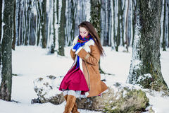 Beautiful woman in sheepskin coat sitting on tree branch in winter forest Stock Photos