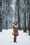 Beautiful woman in sheepskin coat in winter forest Stock Image