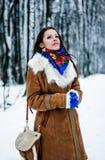 Beautiful woman in sheepskin coat in winter forest Stock Image