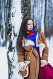 Beautiful woman in sheepskin coat in winter forest Stock Images