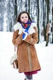 Beautiful woman in sheepskin coat in winter forest Stock Photo