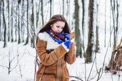 Beautiful woman in sheepskin coat in winter forest looking in mirror Royalty Free Stock Photo