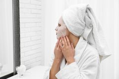 Beautiful woman with sheet mask on her face at mirror stock photo