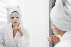 Beautiful woman with sheet mask on her face at mirror stock photography