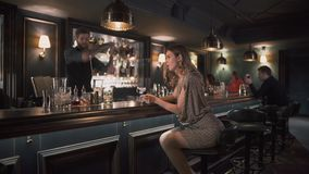 Beautiful girl in shiny dress making selfie sitting at the bar counter. In the background tall bearded bartender shaking. Beautiful woman in shiny dress making stock video