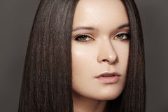 Beautiful woman with shiny straight hair, fashion make-up. Beautiful woman model with perfect dark hair style, natural eye make-up and pale lips, clean skin on royalty free stock image