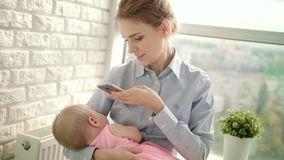 Beautiful woman in shirt taking mobile photo of girl. Mom taking photo of baby stock footage