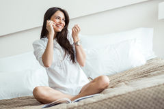 Beautiful woman in a shirt talking on the phone and reading on a Royalty Free Stock Photo