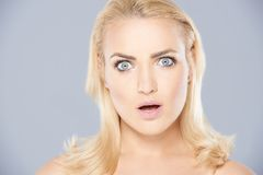 Beautiful woman with a shocked expression. Beautiful blond woman with blue eyes with a shocked expression and her mouth open on a grey studio background royalty free stock image