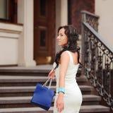 Beautiful  woman with shopping bag. Rich girl. Cute woman  in white dress with shopping bag Stock Photography