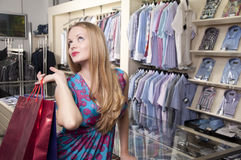 Beautiful woman with shopping bags. In the mall, Thinks about purchases Stock Photo