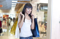 Beautiful woman with shopping bags. In the mall, Thinks about purchases Stock Images