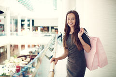 Beautiful woman with shopping bags in big mall. Royalty Free Stock Image