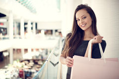 Beautiful woman with shopping bags in big mall. Happy beautiful woman with shopping bags stands at shop. Attractive caucasian girl with purchasing bags in big royalty free stock photos