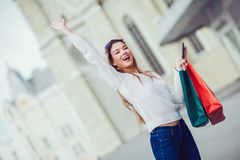 Beautiful woman with shopping bags in the city. Using digital tablet Royalty Free Stock Image