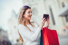 Beautiful woman with shopping bags in the city. Using digital tablet Stock Photo