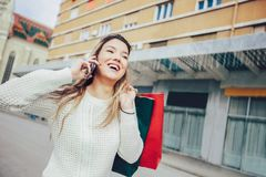Beautiful woman with shopping bags in the city. Using smart phone Royalty Free Stock Photo