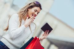 Beautiful woman with shopping bags in the city. Using digital tablet Royalty Free Stock Images