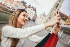 Beautiful woman with shopping bags in the city using smart phone. Make selfie photo Royalty Free Stock Photography
