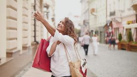 Beautiful woman with shopping bags in the city using smart phone make selfie photo. Slow motion.  stock footage