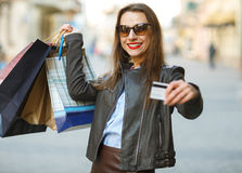 Beautiful woman with shopping bags and credit card in the hands Royalty Free Stock Photos