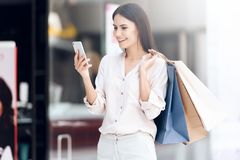 Beautiful woman with shopping bags looking into cell phone. Shopping concept Stock Images