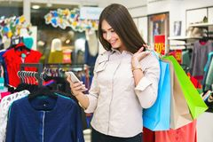 Beautiful woman with shopping bags looking at her phone. Beautiful woman with shopping bags looking at her phone while going out on a shopping spree Stock Images