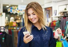 Beautiful woman with shopping bags looking at her phone. Beautiful woman with shopping bags looking at her phone while going out on a shopping spree Stock Image