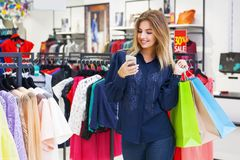 Beautiful woman with shopping bags looking at her phone. Beautiful woman with shopping bags looking at her phone while going out on a shopping spree Royalty Free Stock Images
