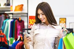 Beautiful woman with shopping bags looking at her phone. Beautiful woman with shopping bags looking at her phone while going out on a shopping spree Royalty Free Stock Photography