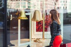 Beautiful woman with shopping bags looking at the shop window Stock Photos