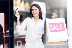 Beautiful woman with shopping bags at mall. Black Friday. Sale. Consumerism concept Stock Photo