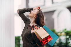 Beautiful woman with shopping bags  smiles and looks happy Royalty Free Stock Photography