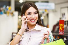 Beautiful woman with shopping bags talking on the phone. Royalty Free Stock Photography