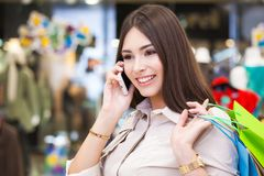 Beautiful woman with shopping bags talking on the phone. Stock Photography