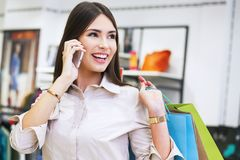 Beautiful woman with shopping bags talking on the phone. Stock Photo