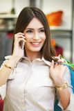 Beautiful woman with shopping bags talking on the phone. Stock Images
