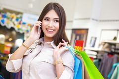 Beautiful woman with shopping bags talking on the phone. Royalty Free Stock Image