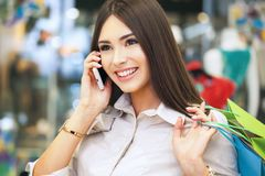 Beautiful woman with shopping bags talking on the phone. Stock Image