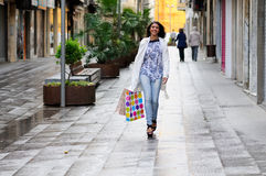 Beautiful woman with shopping bags walking along a commercial st Stock Image