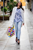 Beautiful woman with shopping bags walking along a commercial st Stock Photo