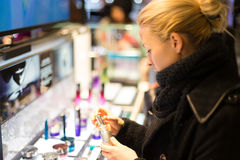 Beautiful woman shopping in beauty store. Royalty Free Stock Photos