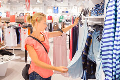 Beautiful woman shopping in clothing store. Royalty Free Stock Images