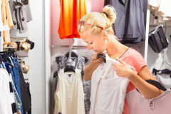 Beautiful woman shopping in clothing store. Royalty Free Stock Photos