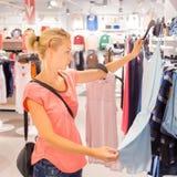 Beautiful woman shopping in clothing store. Stock Photo