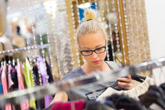 Beautiful woman shopping in clothing store. Royalty Free Stock Photography