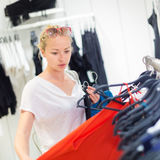 Beautiful woman shopping in clothing store. Stock Images