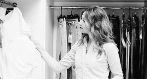 Beautiful woman shopping in clothing store. Consumerism, shopping, lifestyle concept. Seasonal sales. Happy woman in shopping. Bla stock image